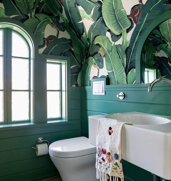 a-bold-retro-bathroom-with-banana-leaf-wallpaper-on-the-ceiling-emerald-paneling-a-floating-vanity-and-arched-windows